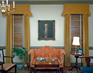 A Georgian home displays one of the era's favorite arrangements: richly stained wood blinds framed by cornice-topped floor-length curtains.