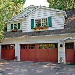 Amidst white siding and green shutters, red garage doors are a bold accent.