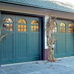 If your goal is to show off your garage door rather than camouflage it, paint it an accent color—here, teal garage doors match other elements on the house, including the entry door and garden gate.
