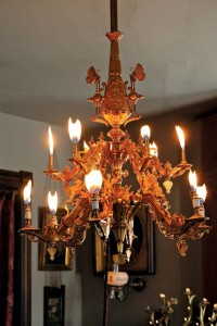 An ornate, gilded bronze gas chandelier has been restored to its original glory, complete with flickering flames.