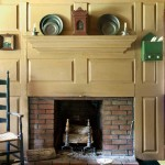 The raised-panel fireplace wall is the focus of the parlor; this reproduction work was recently replaced with an 18th-century paneled wall that retains its original paint.