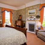 "The master bedroom fireplace retains pictorial Minton tiles called ""The Sporting Scenes of Old England."" Curtains are a playful cantaloupe weave with blue bullion fringe on the pelmets."