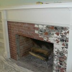 The damaged, plain brick fireplace with faux stone was removed.