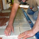 Bill Muscarella makes subtle adjustments to the position of hearth tiles as he lays an accent border.