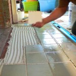 He lays tile quickly once the mortar is spread, continually checking for lippage (a difference in height from one tile to the next).