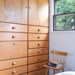 In the bedroom, a sleek wall of built-in drawers and closets retains the original finger pulls.