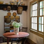 A breakfast nook in the kitchen is furnished with a ca. 1840 drop-leaf tavern table with its original red paint, old farmhouse chairs, and racks holding vintage cutting boards and hickory baskets.