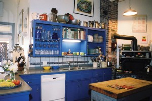 Margaret and Howard run the breakfast portion of their B&B courtesy of a new, highly efficient wood-burning stove with an antique look. With its open shelving and base cabinetry painted a vibrant, electric blue, the kitchen is a cheerful spot for any artist to start the day.