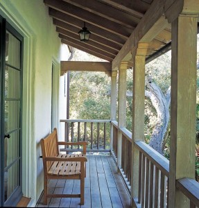 The timber balcony off the second-floor master suite is detailed in the Spanish colonial style.