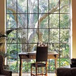 The floor-to-ceiling window frames an old oak tree beyond.