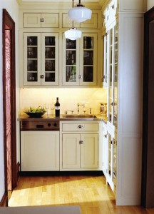 Crown Point used a mix of glass-front and solid cabinets in this pantry, outfitted with a sink and dishwasher.