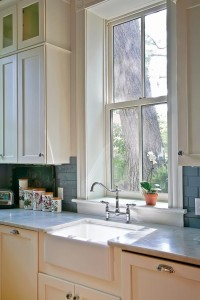 Blue subway tiles add a splash of color to the otherwise neutral palette. A white farmhouse sink and marble countertop create an Old World look in the room.
