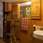 Knotty pine walls warm a first-floor guest bedroom just off the main living room.
