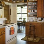 The kitchen's pine cabinets and original maple floors were recently restored; the room has cooking utensils and Tea Leaf pattern plates collected over generations. The dining porch is just beyond.