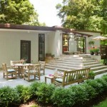 The south façade is anchored by a wide patio and deck; sliding glass doors are original.