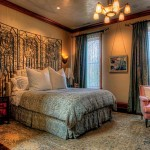 Jean created a sumptuous master bedroom with silk-covered walls, a headboard that incorporates an antique screen, and stunning light fixtures.
