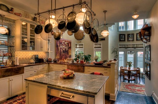 At the back of the house, the kitchen, with holophane-style lights and farmhouse sinks, opens onto the breakfast room