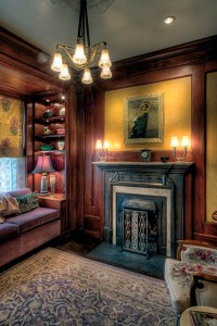 The completed parlor elegantly expresses the collaboration between client, architect, and designer. Architect Kathryn Quinn defined the space with dark-stained woodwork and built-ins, which are brought to life by Jean's dramatic orchestration of color. An antique French portrait over the Art Deco fire surround makes a stunning focal point.