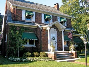 White-trimmed green awnings provide subtle contrast on a Colonial Revival house.