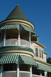 Striped awnings protect a beachside Queen Anne.