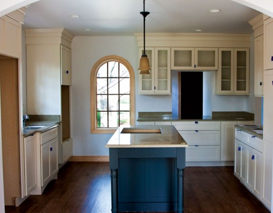 Before work began, the kitchen was in such bad shape that no appliances remained. The finished room retains an arched entryway and radius window, while adding new cabinets and countertops.