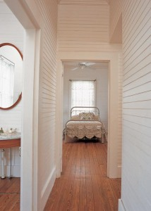 On the main level behind the stair, a narrow hall connects the two downstairs bedrooms. The simple, restrained palette of the rest of the house—stained, polished floor and white-painted beadboard— continues into these semi-hidden rooms.