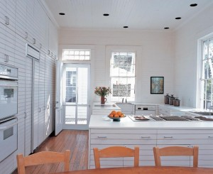 Although this is the kitchen of a professional cook, it purposefully has the feel of a home kitchen. With a restrained white palette and no-nonsense stainless hardware and trim on the appliances, this is a simple, modern look in a traditional home. The polished old heart pine floor provides a warm contrast with the otherwise all-white room.