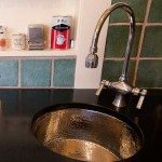 The Kohler butler's sink used near the range was a showroom model, purchased on sale. Chicago Faucets still makes parts for their 80-year-old fixtures, like this salvaged faucet. Countertops are honed granite.
