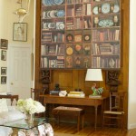Trompe l'oeil library paper decorates a set of massive pocket doors used as a wall.