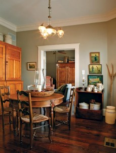 The breakfast room, thought to be the original back porch, features a late-1800s English oak armoire that supplies storage space. The dry sink at right displays circa-1893 Texas Marshall Pottery.
