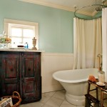 Leonard and Kevin replaced the turquoise fixtures in the guest bath with an antique painted sideboard, new wainscoting, and a period-style pedestal tub.