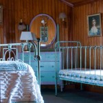 More cottage furniture accompanies a metal bed and crib in a bedroom with a chenille spread and the promise of a good sleep in the mountain air.
