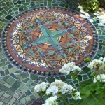 Multiple-tile mural compass, border, and broken mosaic surround on a patio, by RTK Studios.