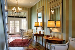 With bold striped walls and antique furnishings, the entry to the main house is eclectic yet soothing.