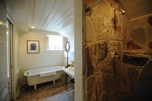 In the bathroom of the Meriwether Suite, a clawfoot tub shares space with a luxurious stone-lined shower.