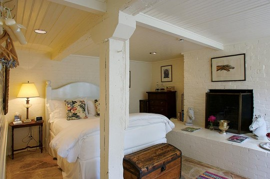 In the Meriwether Suite, situated in what was once storage space under the carriage house, artifacts from the Meriwether Lewis House mingle with original wooden beams and brickwork.
