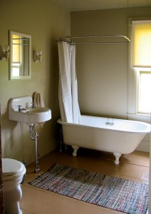 he sink and sconces in Patrick and Joyce's bath were salvage finds; the toilet was rescued from a friend's house and restored.
