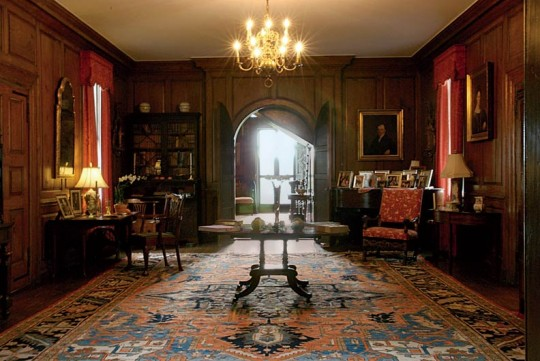 Unusual arched doors are a focal point of the great hall. The room's antiques and Scalamandré curtains are period-appropriate.