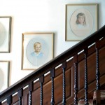 Behind turned balusters on stairs once traveled by a young Thomas Jefferson hang portraits of the Thompson children, part of the next generation of caretakers.