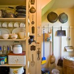 The re-created pantry houses the fridge, microwave oven, and toaster, along with vintage appliances, and tin, graniteware, enamelware, and stoneware.