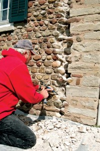 Marty began the repairs by carefully removing old caulk, mortar, and rubble stone with a hammer and chisel. The cobblestones were set aside and later fitted back into the wall.