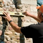 To replicate the distinctive V-shaped joints around the cobblestones, Marty started by using a level and trowel to create horizontal grooves between each course of stones.