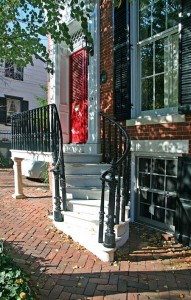 The curved stone steps and platform, accented with an an ornate cast-iron railing, are distinguised mid-19th-century additions to this Prince Street house.