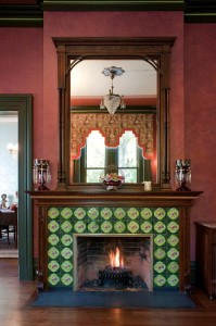 Green and pink 19th-century tiles, found in a salvage yard in New York City, surround the breakfast room fireplace. The mahogany mantel's carved rope motif repeats in moldings and other architectural elements throughout the house.