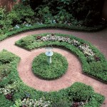 Formal beds and radiating bricks encircle a sundial.