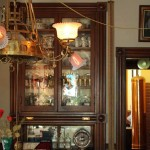 Behind the back parlor, the dining room brims with Victorian china displayed in restored cabinets. The combination gas/electric fixture, discovered in a shop, is original to the room.