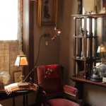 A gas wall bracket lights a reading chair in the front parlor.