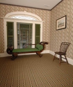 A geometric ingrain carpet in four colors installed wall-to-wall in a historic Federal-period mansion in Hudson, New York. The wallpaper was hand block-printed by Adelphi Paper Hangings.