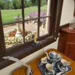 A porringer-top table sits under a garden-facing window.