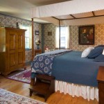 New England at the late 18th/early 19th century features low ceilings, a simple canopy and bedskirt, folk-art portraits, and documented wallpaper found on Martha's Vineyard.